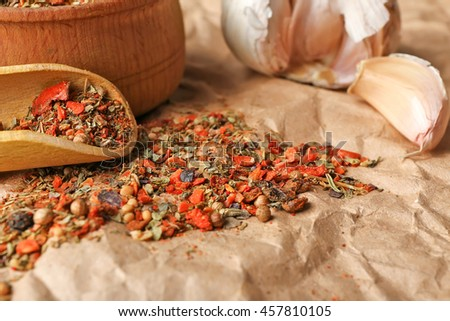 Mixed spices in wooden scoop on parchment - stock photo