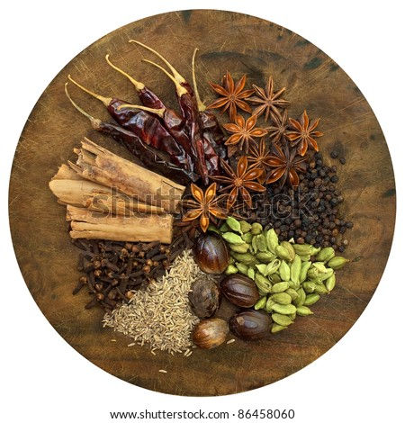 Mixed spices on a wooden chopping board - stock photo