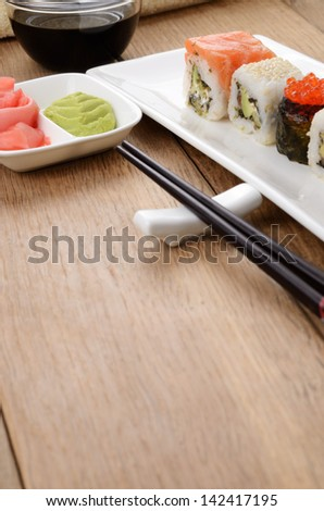 Mixed sushi on a white plate with soy sauce wasabi and ginger - stock photo