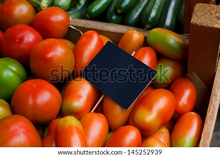 Mixed tomatoes in a wooden box on display - stock photo