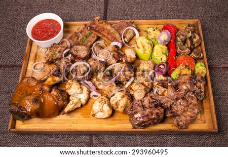Mixed various grilled meat platter with vegetables and spicy tomato sauce. Located on a brown canvas tablecloth background. - stock photo