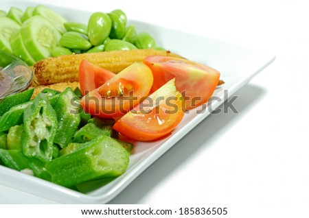 Mixed vegetable menu with sliced cucumber, tomatoes, grilled baby corn, boiled okra and fresh stink beans mostly served with Shrimp-paste sauce in Thai food menu.