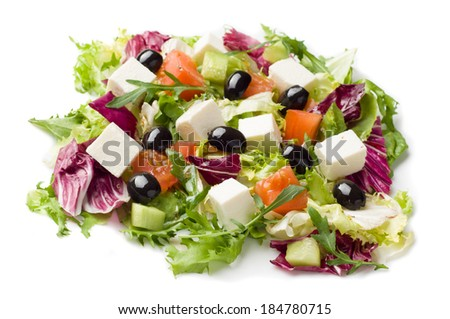 Mixed vegetable salad wit olives and feta cheese on white plate