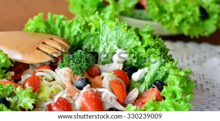 Mixed vegetable salad with chicken on a white bowl on a wooden table