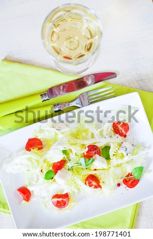 Mixed vegetable salad with the glass of white wine - stock photo