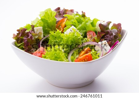 mixed vegetable salad with tomatoes, onions and feta cheese in a white bowl on white background - stock photo