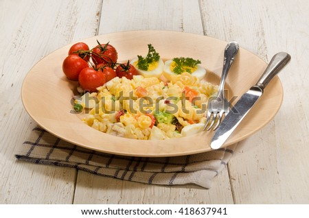 mixed vegetarian pasta salad with egg and vegetables on a wooden plate - stock photo