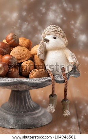 Mixed whole nuts with Christmas ornament - selective focus on almond nut in dish with shallow dof - stock photo
