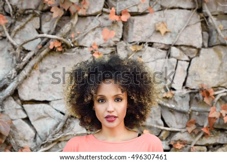 Mixed woman with afro hairstyle standing in an urban park