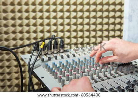 Mixer board and man hands in recording studio.