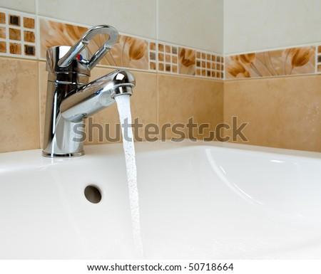 mixer tap with running water - stock photo
