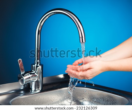 mixer tap with water and washing hands, blue background - stock photo