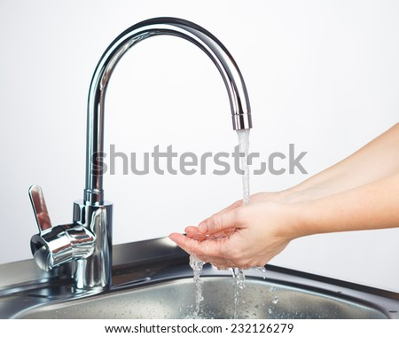 mixer tap with water and washing hands, light background - stock photo