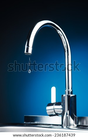 mixer tap with water drops, blue background - stock photo