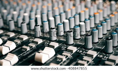 Mixing Board Sound Knobs. Pro audio mixing board faders and knobs, multi-track music recording equipment. - stock photo