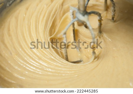 Mixing egg, flour and sugar cream in bowl with motor mixer. Kneaded dough for baking a cake  - stock photo