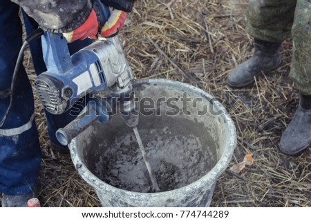 Mixing plaster solution in a bucket using electric drill. Construction and renovation concept.