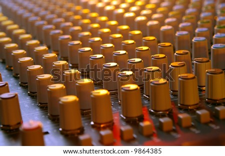 mixing soundboard under multi-colored lights - stock photo