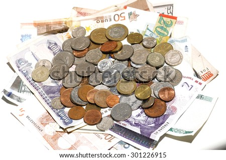 mixture of banknotes and coins from several countries on white background - stock photo