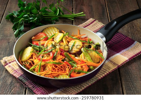 Mixture of roasted vegetables in a frying pan on a napkin and parsley on a wooden table