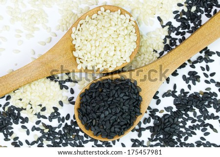 Mixture of white and black sesame on wooden spoons - stock photo