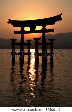 Miyajima gate silhouette at sunset. In the background the mountain range of Hirodenmiyahimaguchi/Hiroshima Prefecture. - stock photo