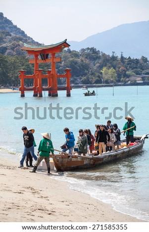 MIYAJIMA, JAPAN - CIRCA APR, 2013: Visitors go to the beach from the boat after sea cruise near the torii gate. The Miyajima Island (Itsukushima), Japan - stock photo