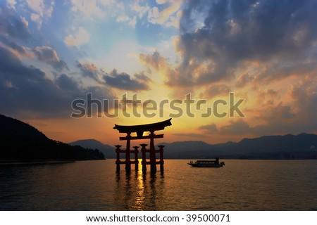 Miyajima Torii silhouette at dusk with cruising boat. - stock photo