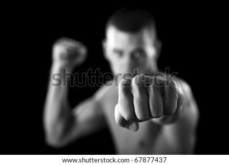 MMA - Mixed martial art warrior  punching.Selective focus on fist. - stock photo
