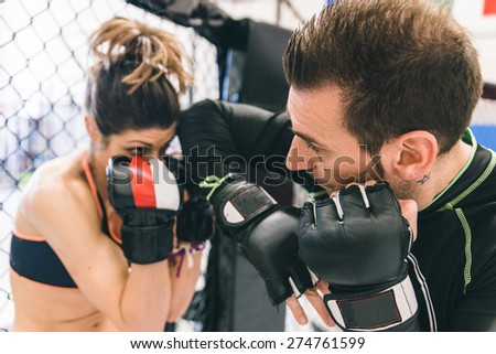 mma training. couple making sparring in the mma cage. concept about fighting, fitness and sport - stock photo