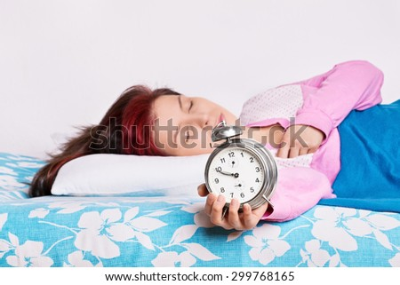 Mmm, one more minute please... Young girl overslept with alarm clock in her hand - stock photo