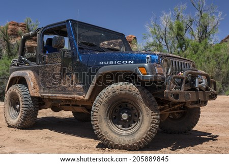 Moab, Utah - May 15, 2014: Muddy jeep on a back country four wheel drive trail in Utah's Canyonlands National Park. - stock photo