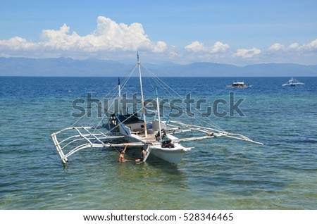 MOALBOAL, CEBU, PHILIPPINES - MAY 27, 2016 - Young couple at bangka boat in the ocean in Moalboal, Philippines, Cebu Island