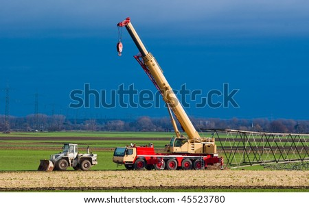Mobil crane preparing for assembling transmission towers, transmission lines on the background - stock photo