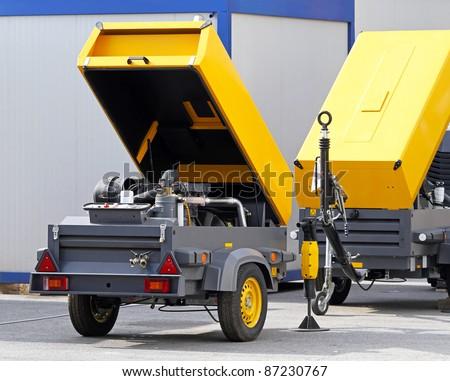 Mobile air compressor unit at construction site - stock photo