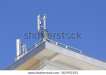 Mobile antenna in a building, against blue sky - stock photo