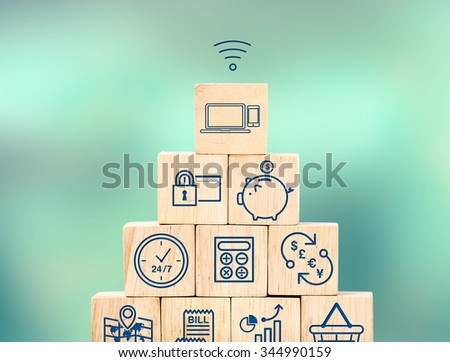 Mobile banking feature icon on wood cube pyramid with blur blur background, Digital marketing concept. - stock photo