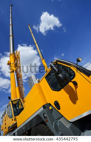 Mobile construction cranes with telescopic arms mounted on trucks with yellow bodyworks in sunny day with white clouds and deep blue sky on background, heavy industry - stock photo
