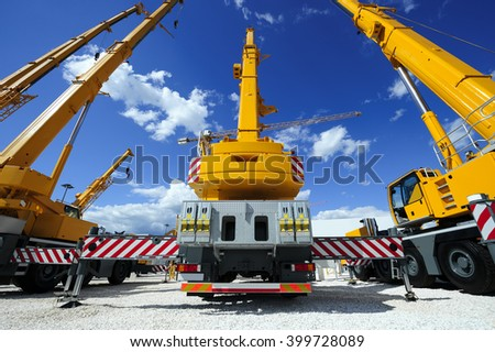 Mobile construction cranes with yellow telescopic arms and big tower cranes in sunny day with white clouds and deep blue sky on background, heavy industry  - stock photo