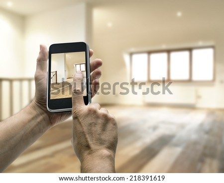 Mobile device with man hands taking picture in modern loft studio - stock photo