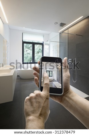 Mobile device with man hands taking picture in  tiled bathroom with windows towards garden, hands on the right side - stock photo