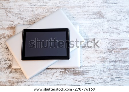 Mobile digital devices. A Tablet PC on some closed Laptop computers. - stock photo