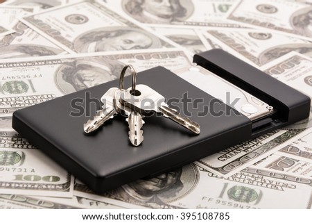 Mobile hard disk and key on the money - stock photo