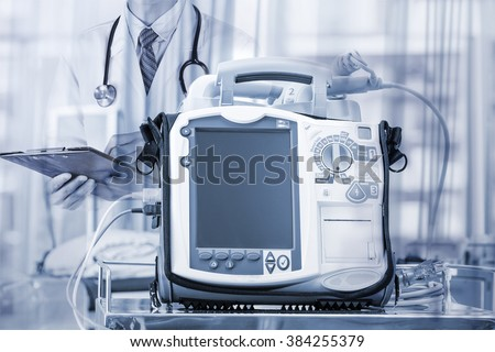 Mobile Heart Defibrillator unit in emergency room with double exposure effect - stock photo