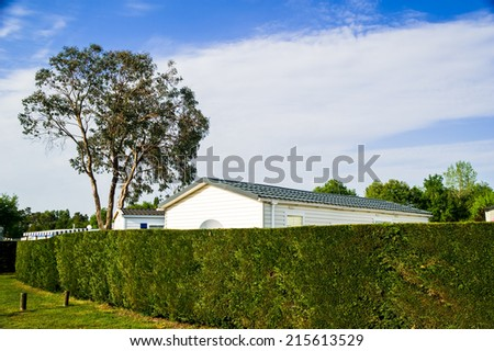 mobile home with a beautiful natural fence - stock photo