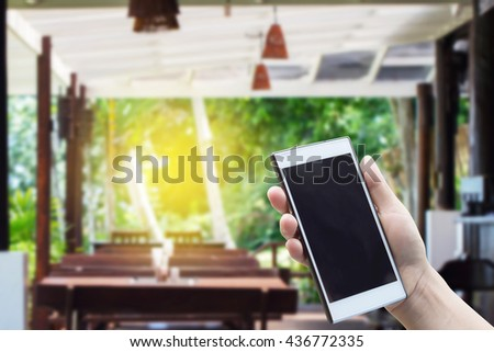 Mobile in hand on the background blurred restaurant. Light Fair. The Business Call to order fast food. - stock photo