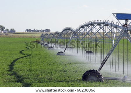 Mobile irrigation machine in action spraying water on crops - stock photo