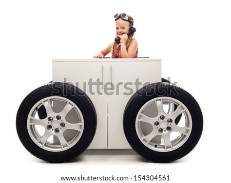 Mobile office concept with little girl on the phone sitting in wheeled box - stock photo
