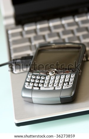 mobile office: PDA on a laptop - stock photo