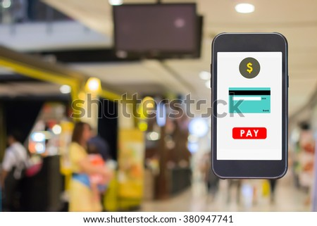 Mobile payment from credit card on the screen with blurred of people are walking in shopping center. - stock photo